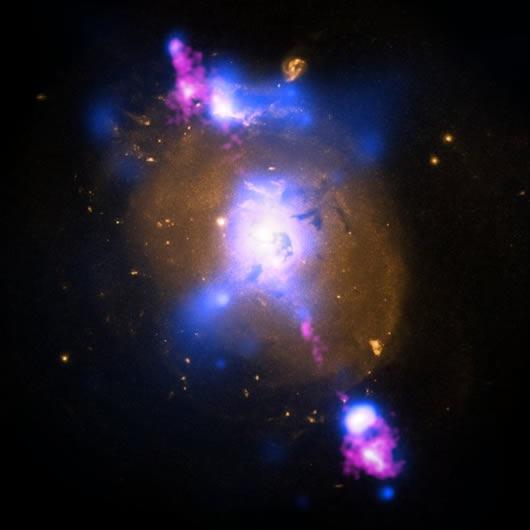 Gökada merkezindeki karadelik çevresinden yayılan jetlerin oluşturduğu renk cümbüşü. Görüntü üç farklı dalga boyunda alınan verilerle oluşturuldu. ( X-ray: NASA/CXC/SAO/A. Siemiginowska et al; Optical: NASA/STScI; Radio: NSF/NRAO/VLA)
